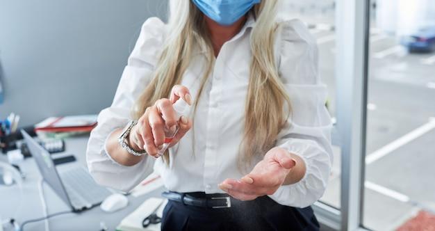 Femme d'affaires avec masque facial et gants à l'aide d'un désinfectant pour les mains au bureau. protection contre le corona virus.