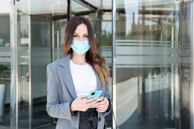 Femme d'affaires avec un masque facial et un smartphone