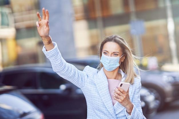 Femme d'affaires en masque prenant un taxi dans la ville. photo de haute qualité