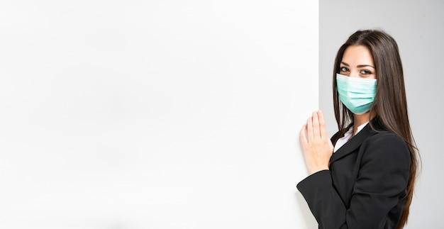 Femme d'affaires masquée en face d'un mur blanc