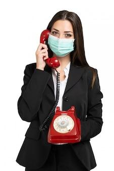 Femme d'affaires masquée utilisant un téléphone vintage pendant la pandémie de coronavirus