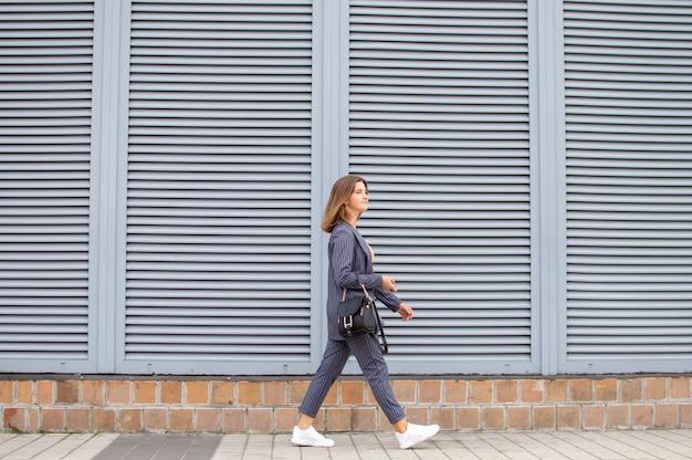 Femme d'affaires le matin va travailler dans la ville contre le mur, une fille en costume rayé marche le long de la rue