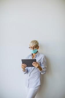 Femme d'affaires mature à l'aide d'une tablette numérique de poche et porter un masque pour prévenir l'infection par le virus corona