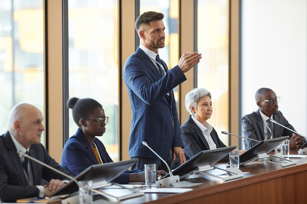 Femme d'affaires mature en costume lors d'une conférence d'affaires pour ses collègues