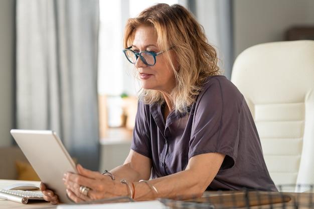 Femme d'affaires mature dans des vêtements décontractés et des lunettes regardant l'écran de la tablette alors qu'il était assis dans un fauteuil par table dans l'environnement familial