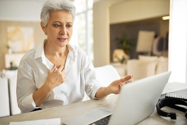 Femme d'affaires mature élégante avec coupe de cheveux courte assis devant un ordinateur portable, regardant l'écran avec la bouche ouverte comme si elle disait quelque chose