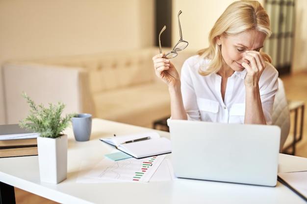 Une femme d'affaires mature et fatiguée a enlevé ses lunettes en massant le pont du nez souffrant de sécheresse oculaire
