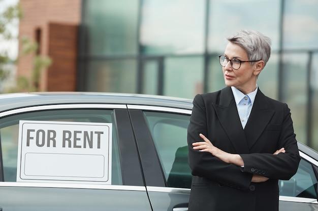 Femme d'affaires mature à lunettes et en costume debout avec les bras croisés et à la voiture, elle loue la voiture