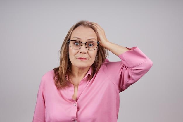 Femme d'affaires mature perplexe avec des lunettes tient sa tête avec sa main