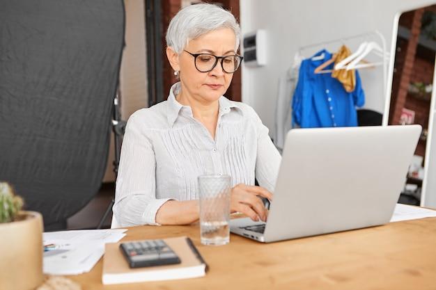 Femme d'affaires mature qualifiée et expérimentée confiante portant des lunettes élégantes, tapant des lettres à ses clients et partenaires commerciaux, en utilisant une connexion internet sans fil haute vitesse sur un ordinateur portable.