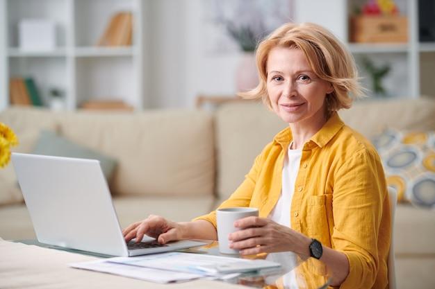 Femme d'affaires mature réussie avec une tasse de thé en vous regardant alors qu'il était assis par un bureau devant un ordinateur portable à la maison pendant la quarantaine