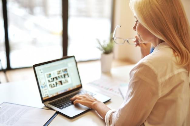 Femme d'affaires mature utilisant un ordinateur portable tout en travaillant au bureau pendant la journée