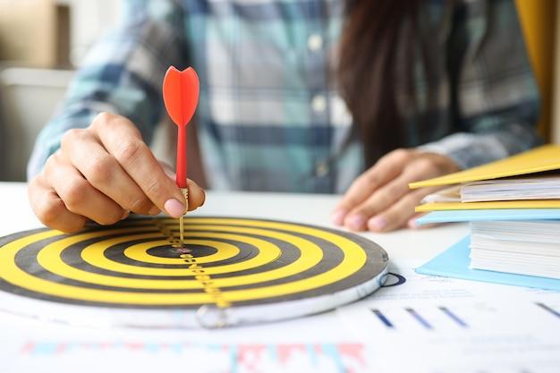 La femme d'affaires met la fléchette au centre des fléchettes sur le lieu de travail au bureau. buts et objectifs en entreprise. concept