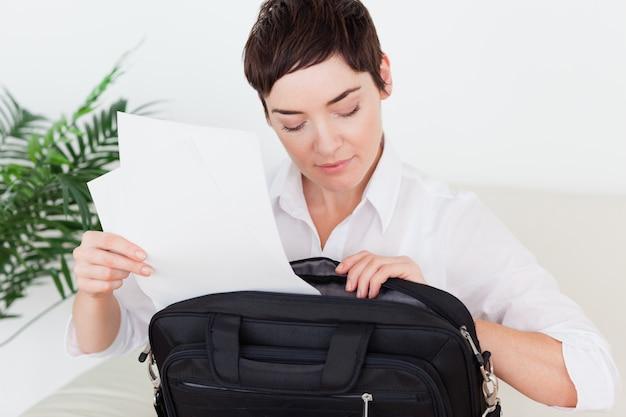 Femme d'affaires mettant des papiers dans son sac