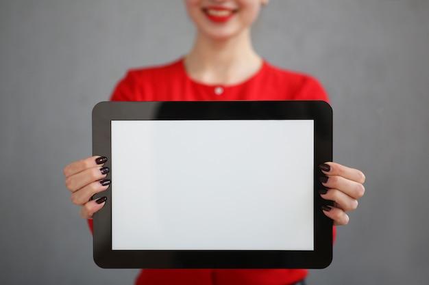 Femme d'affaires de mode avec une chemise rouge et un portrait de lunettes, tenant une tablette dans ses mains