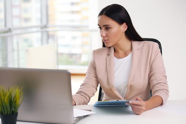 Femme d'affaires modèle assez féminin. employé de bureau professionnel confiant.