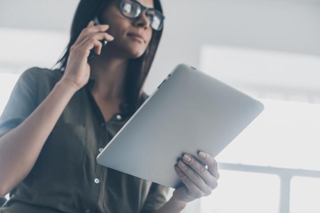 Femme d'affaires moderne au travail. low angle view of confiant young woman in smart casual wear parlant au téléphone mobile et tenant une tablette numérique
