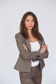 Femme d'affaires moderne en costume avec ses bras croisés debout sur fond gris.