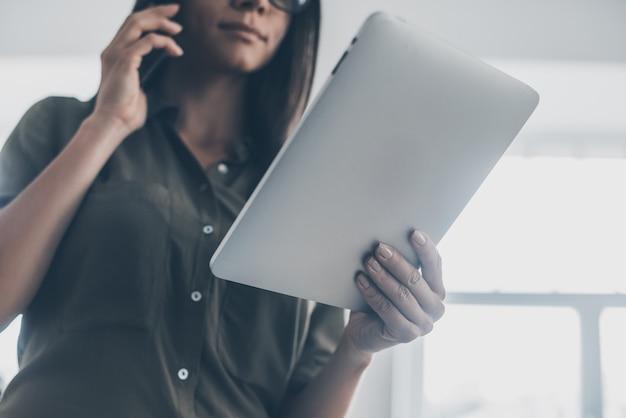 Femme d'affaires moderne. low angle view of confiant young woman in smart casual wear parlant au téléphone mobile et tenant une tablette numérique