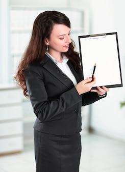 Femme d'affaires moderne pointant sur une feuille vierge