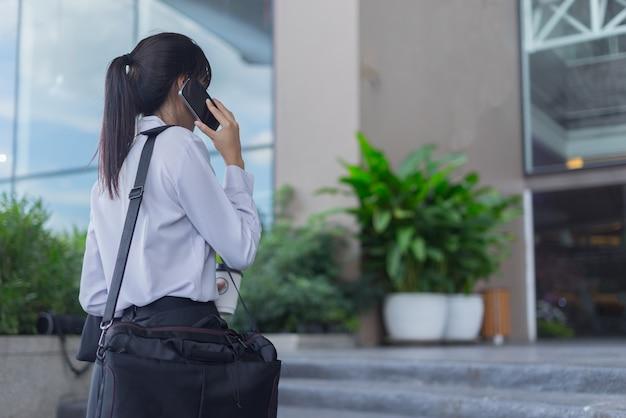 Femme d'affaires moderne travaillant avec un smartphone en plein air