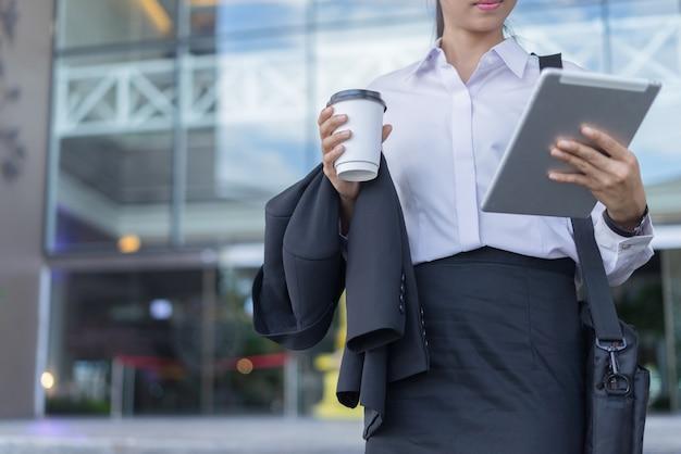 Femme d'affaires moderne travaillant avec tablette en plein air
