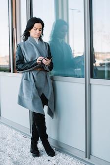 Femme d'affaires moderne utilisant un smartphone à l'extérieur
