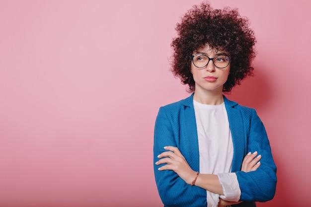 Femme d'affaires moderne vêtue d'une veste bleue et porte des lunettes pose sur rose avec des émotions insatisfaites