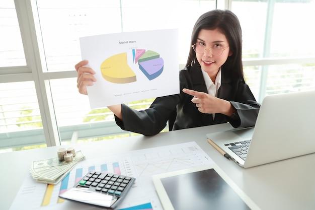 Femme d'affaires montrant les bénéfices de l'entreprise avec graphique dans la salle de réunion
