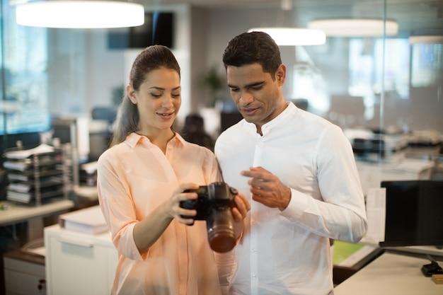 Femme d'affaires montrant la caméra à un collègue au bureau