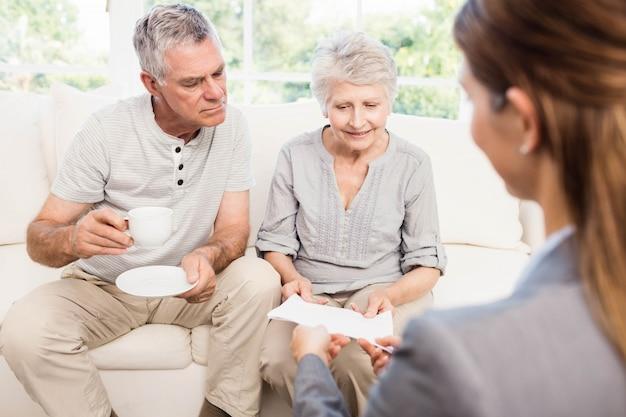 Femme d'affaires montrant des documents au couple de personnes âgées à la maison
