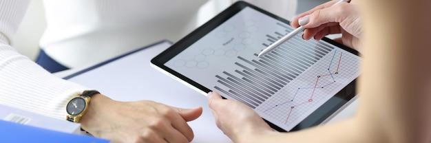 Femme d'affaires montrant un graphique de collègue sur une tablette numérique en gros plan