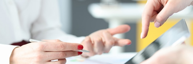 Femme d'affaires montrant des informations à un collègue sur l'innovation commerciale en gros plan sur une tablette numérique