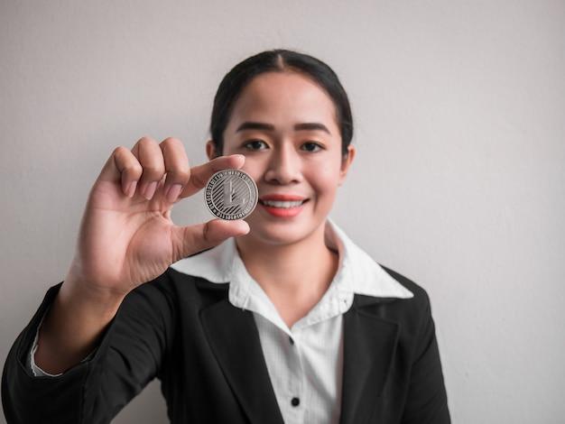 Femme d'affaires montrant un litecoin d'argent.