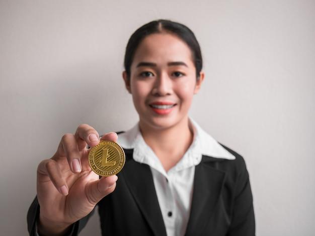Femme d'affaires montrant un litecoin en or.