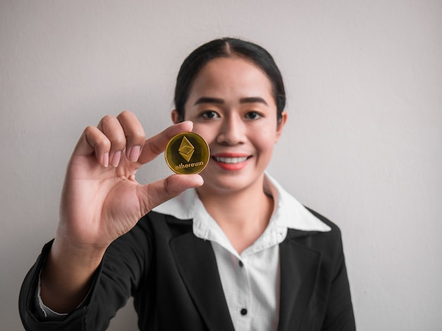Femme d'affaires montrant une pièce d'or ethereum.