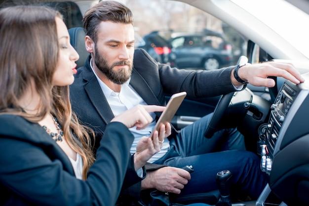 Femme d'affaires montrant le téléphone à l'homme d'affaires assis ensemble à l'avant de la voiture
