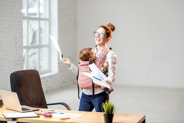 Femme d'affaires multitâche tenant une pile de documents papier avec son bébé debout au bureau
