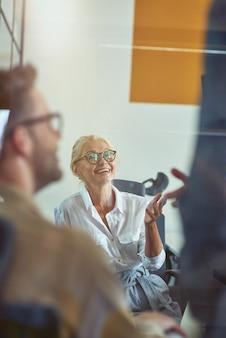 Femme d'affaires mûre gaie discutant de quelque chose avec des collègues et souriant tout en ayant un