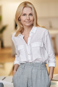 Femme d'affaires mûre intelligente de dame moderne avec des cheveux blonds regardant la caméra tout en se tenant à l'intérieur