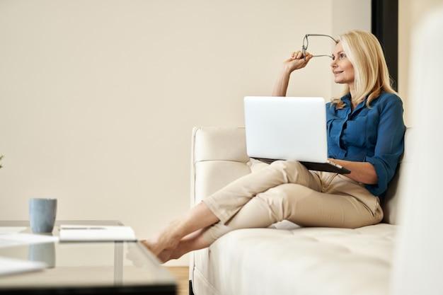 Femme d'affaires mûre pensive souriant loin tout en travaillant à domicile assis sur un canapé dans un style moderne
