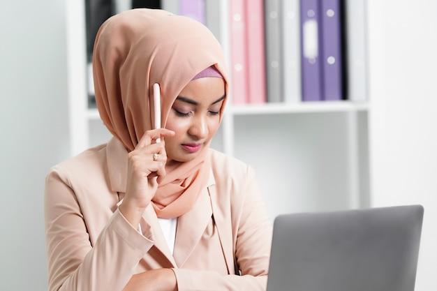Femme d'affaires musulmane pense au travail et à l'idée au bureau.