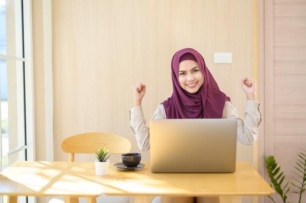 Une femme d'affaires musulmane portant le hijab travaillant avec son ordinateur portable dans un café