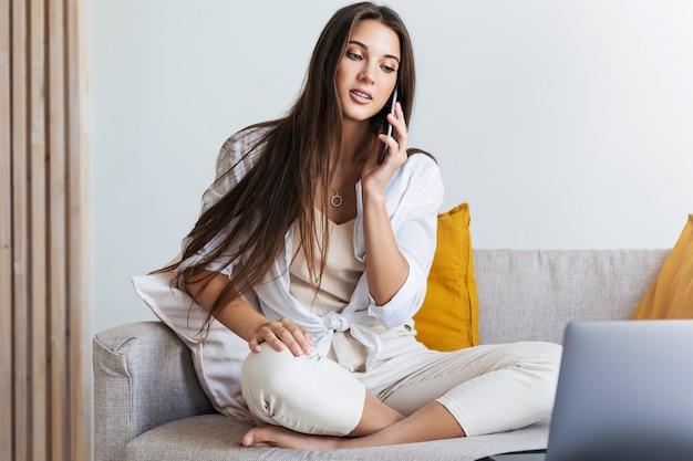 Femme d'affaires négocie au téléphone, en utilisant un ordinateur portable, en naviguant sur internet, à la recherche de contenu utile pour la formation, le travail.