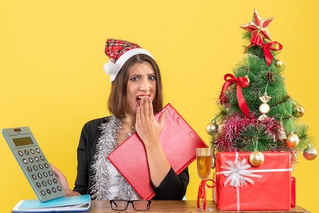 Femme d'affaires nerveuse en costume avec chapeau de père noël et décorations de nouvel an pointant la calculatrice et assis à une table avec un arbre de noël dessus dans le bureau
