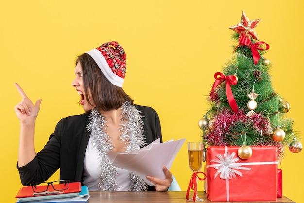 Femme d'affaires nerveuse émotionnelle en costume avec chapeau de père noël et décorations de nouvel an tenant des documents et assis à une table avec un arbre de noël dessus dans le bureau