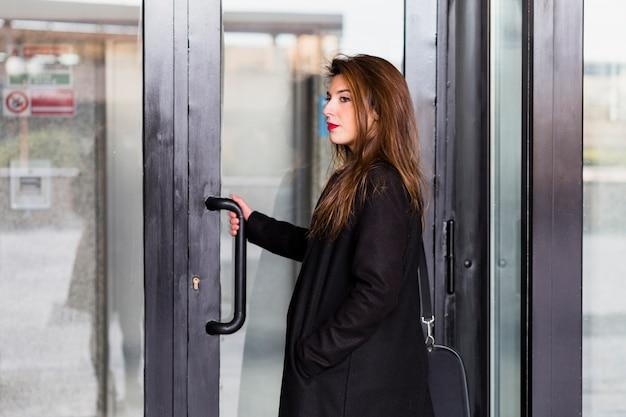 Femme d'affaires en noir entrant dans le bâtiment
