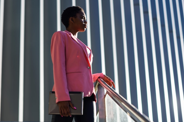 Femme d'affaires noire debout près d'un immeuble de bureaux.