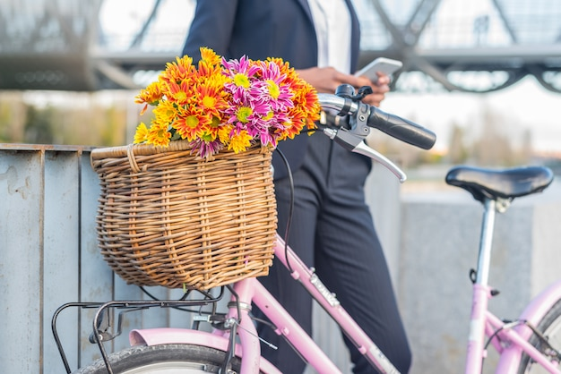 Femme d'affaires noire debout près de son vélo vintage parlant au téléphone mobile
