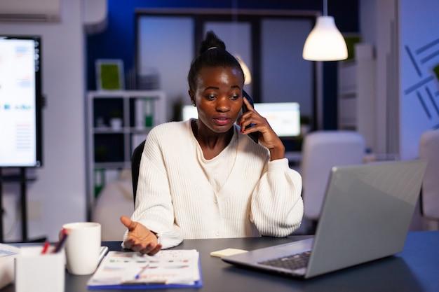Une femme d'affaires noire discute d'un projet important lors d'un appel téléphonique